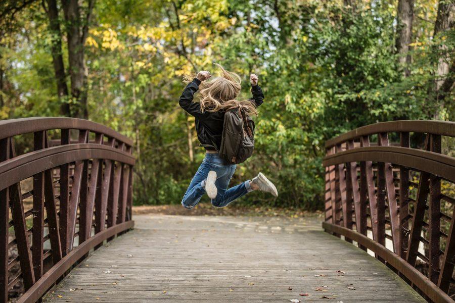 Mädchen auf einer Brücke springt in die Luft
