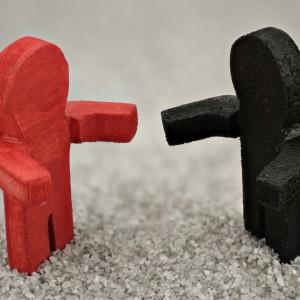 links steht ein rotes Holzmännchen und rechts ein schwarzes