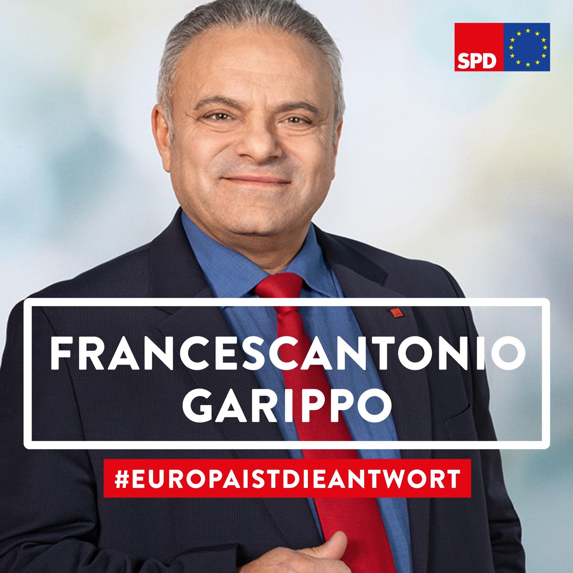 Das Bild zeigt ein Porträt unseres Europa-Kandidaten Francescantonio Garippo in der Halbtotalen. Francescantonio Garippo steht lachend vor einem pastellfarbenem Hintergrund.